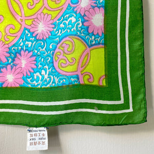 Corner detail of bright green psychedelic scarf showing tiny hole in border