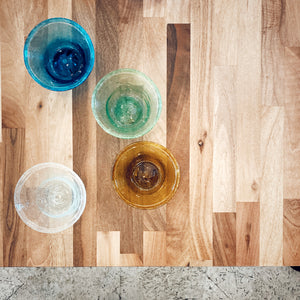 Aerial view of Ishkar's handblown coloured glass tumblers on wooden surface
