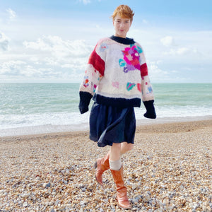 1980s floral jumper, navy skirt and tan boots on redhead model at the beach, sea in background