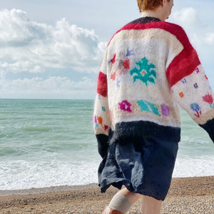 Back view of 1980s floral jumper and navy skirt on redhead model at the beach, sea in background
