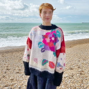 1980s floral jumper and navy skirt on redhead model at the beach, sea in background
