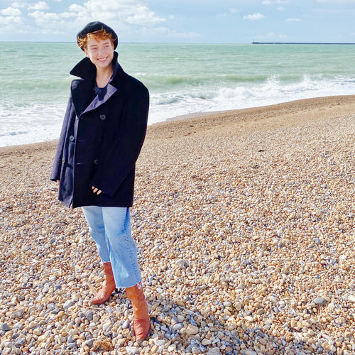 Smiling redhead model on beach with sea in background wearing US Navy pea coat, navy hat, blue jeans and tan boots