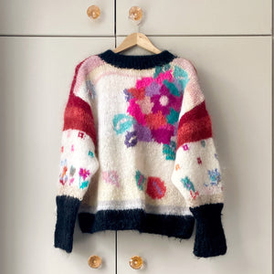 1980s floral jumper on a hanger with taupe wardrobe in background
