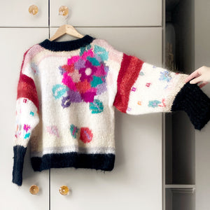 1980s floral jumper on a hanger with taupe wardrobe in background and hand lifting right sleeve