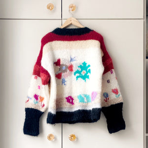 Back view of 1980s floral jumper on a hanger with taupe wardrobe in background