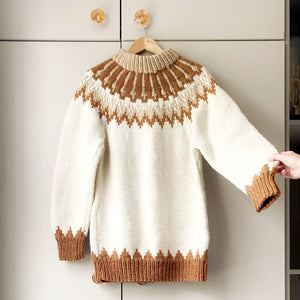 Cream, beige and rust-coloured Shetland jumper on a hanger against a taupe wardrobe with a hand lifting the arm to the right