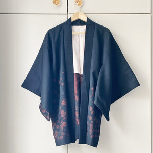 Vintage black wool kimono jacket with metallic border design on wooden hanger against taupe wardrobe