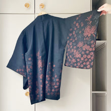 Load image into Gallery viewer, Back view of vintage black wool kimono jacket with metallic border design on wooden hanger against taupe wardrobe, right arm lifted