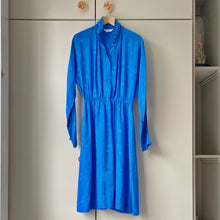 Load image into Gallery viewer, Sapphire blue vintage silk dress on wooden hanger against taupe wardrobe