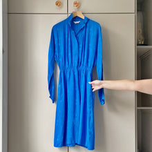 Load image into Gallery viewer, Sapphire blue vintage silk dress on wooden hanger against taupe wardrobe with hand showing pocket