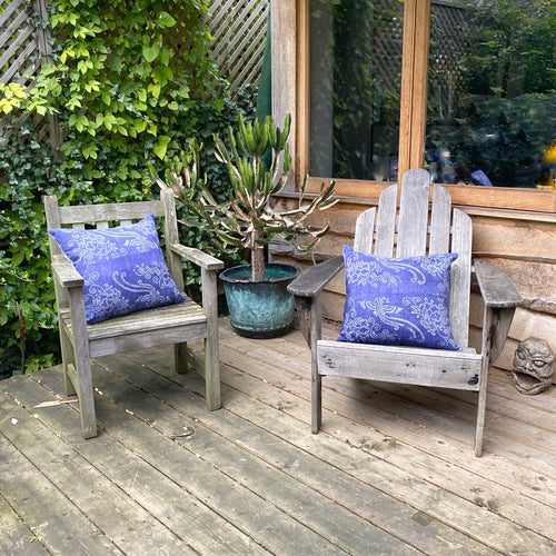 Pair of mismatched wooden chairs on decking with plants in the background and Chinese indigo cushions on seats