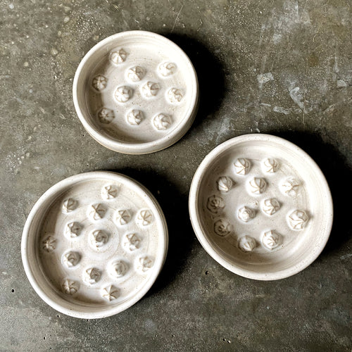 Three Plum & Belle Stud ceramic soap dishes on a polished concrete worktop