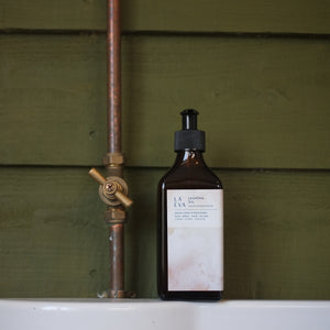LA-EVA JASMĪNA oil in brown apothecary bottle against forest green shiplap panels and copper pipe on white shelf