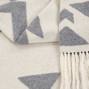 Close-up of Thread Tales Geo Nomad jacquard grey and cream blanket wrap with cream fringe