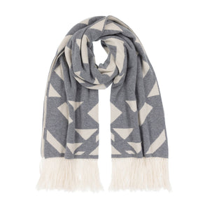 Thread Tales Geo Nomad jacquard grey and cream blanket wrap with cream fringe curled in a loop on a white background
