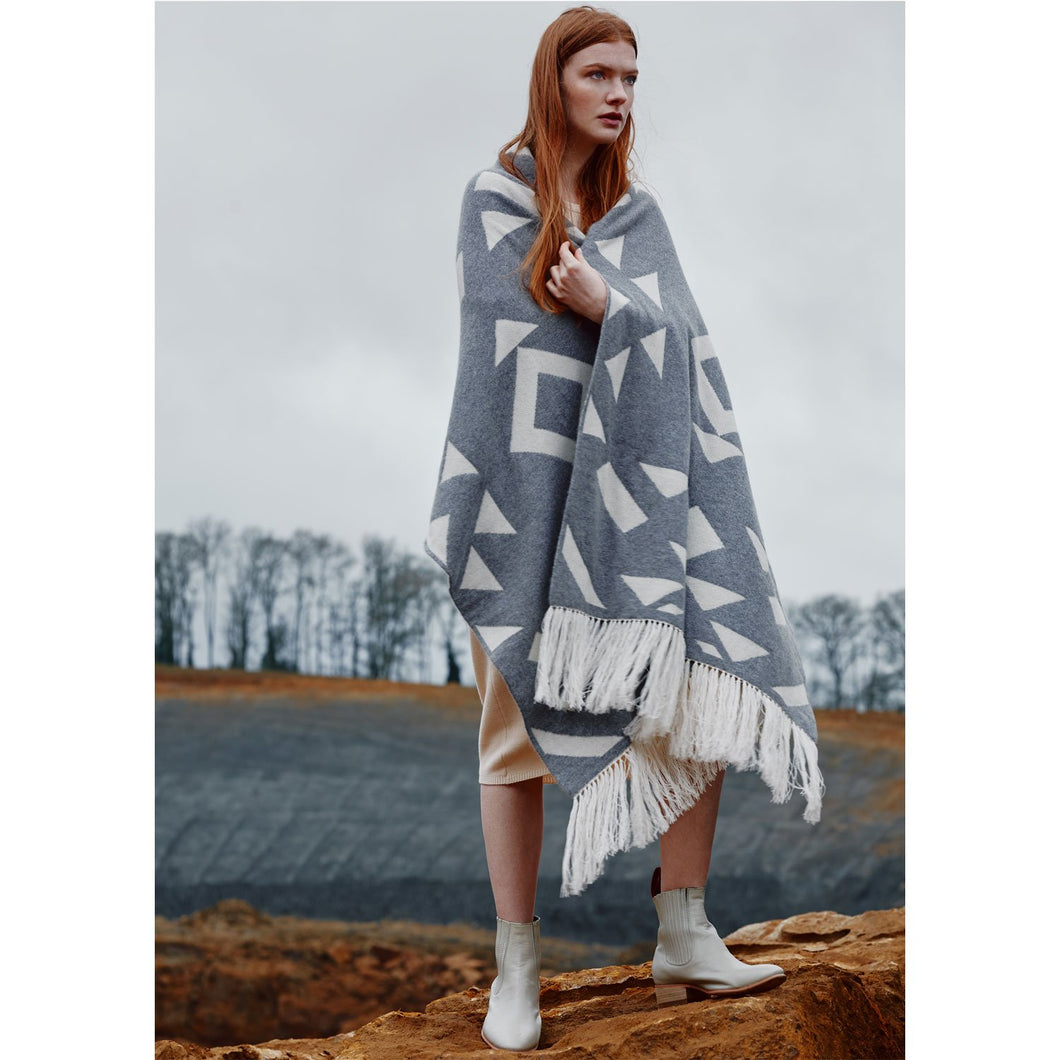 Girl with long auburn hair standing on rock wrapped in Thread Tales Geo Nomad jacquard grey and cream blanket wrap with cream fringe