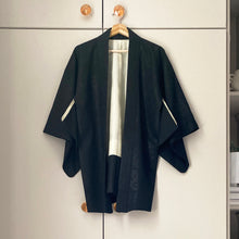 Load image into Gallery viewer, Vintage black kimono jacket with cream lining hanging against a taupe wardrobe background