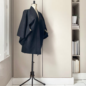Vintage black kimono jacket with cream lining on a tailor's dummy stand with a taupe wardrobe background