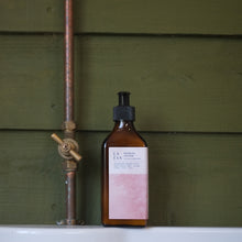 Load image into Gallery viewer, LA-EVA ROSĒUM lotion in brown apothecary bottle against forest green shiplap panels and copper pipe on white shelf