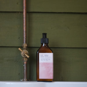 LA-EVA ROSĒUM lotion in brown apothecary bottle against forest green shiplap panels and copper pipe on white shelf