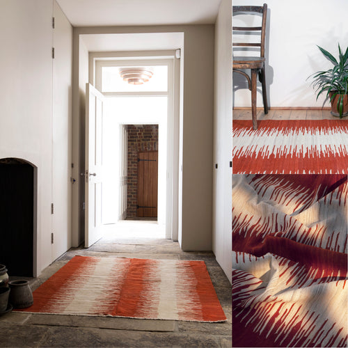 Ishkar's red and cream striped Anar kilim on a flagstone floor with an open door in the background