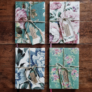 Quartet of Forget Me Not Originals vintage textile bound journals, each tied with string and a matching label on a wooden background