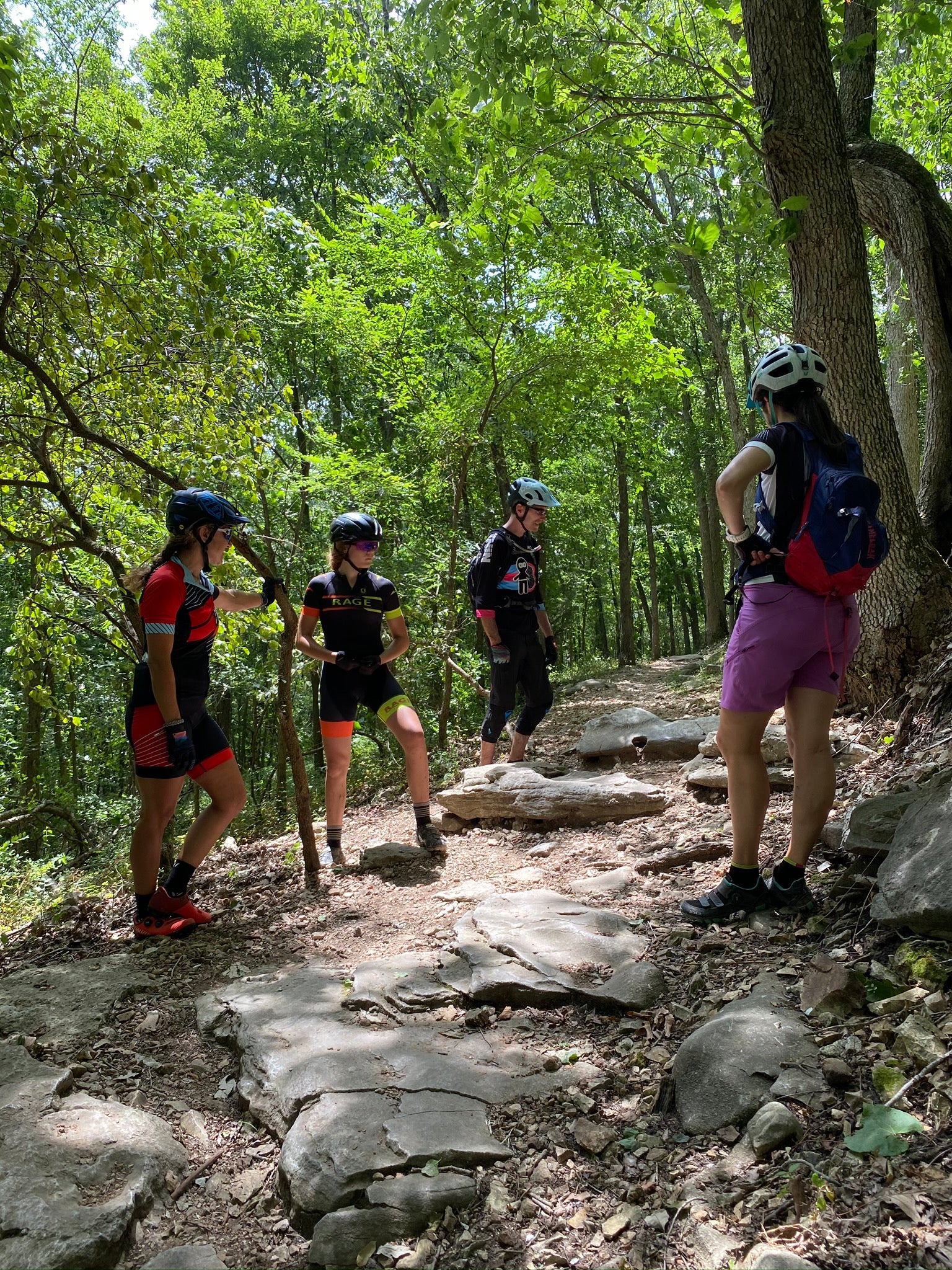 Skills class breaks down technical rock section on mountain bike trail at Slaughter Pen