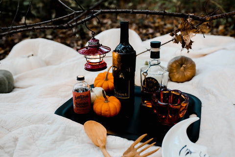 Fall picnic setting with wine, pumpkins, bourbon in the woods