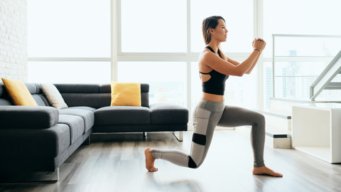 healthy woman exercising by doing lunges in her home