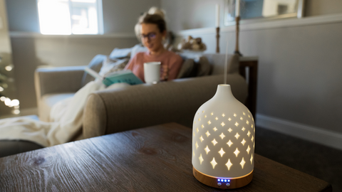 woman relaxing in her home with essential oil diffuser