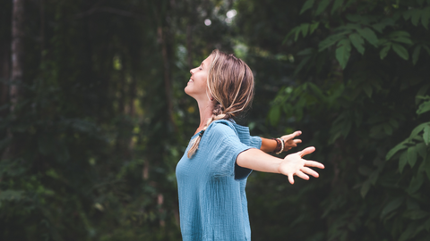 happy woman with open arms experiencing a cedar forest and its benefits