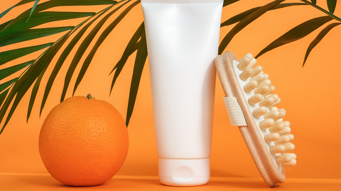 handheld fascia blaster with lotion and orange representing cellulite