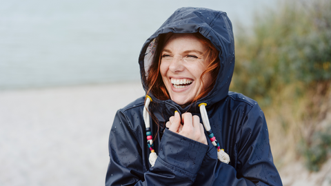 happy woman on cold beach healthy protected against winter illness