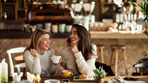 happy women chatting over coffee in a quaint cafe