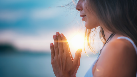 clear-skinned woman meditating at sunset