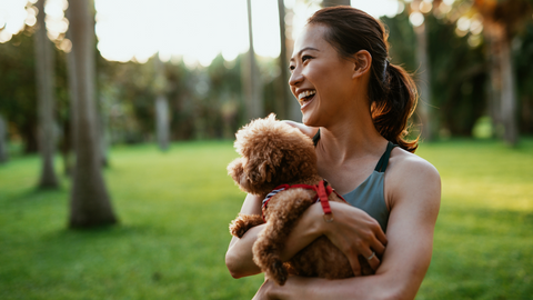 happy woman in a park with her puppy