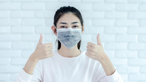 smiling woman wearing a face mask properly and giving a thumbs up