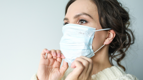 careful woman putting face mask on