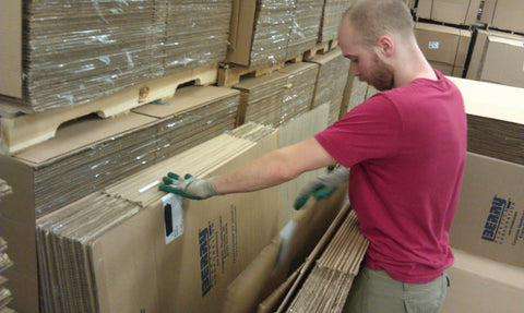 Person sorting used cardboard moving boxes, inspecting for quality prior to packing into UsedCardboardBoxes Earth-Friendly Moving Kits
