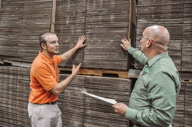 Zac Fratkin and Marty Metro at UsedCardboardBoxes warehouse in front of thousands of used moving boxes, having a discussion.