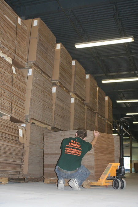 Zac Fratkin at UsedCardboardBoxes warehouse, in front of tens of thousands of used cardboard boxes, stacking used moving boxes after inspections for quality and integrity.