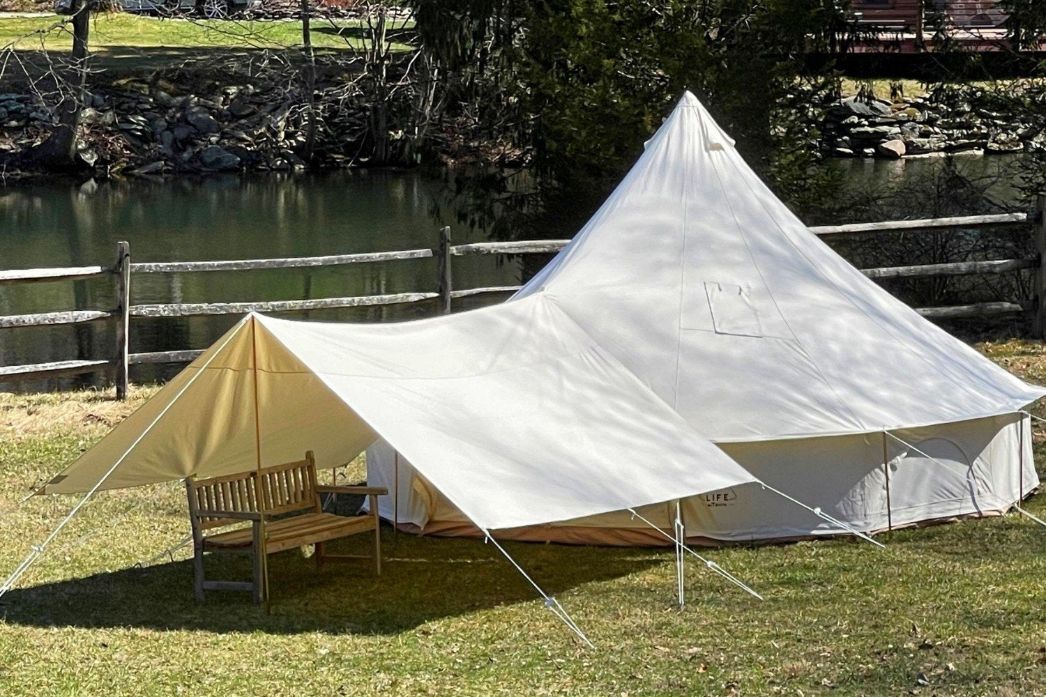 A canvas bell tent with an awning that provides extra space and shade in order to keep cool.