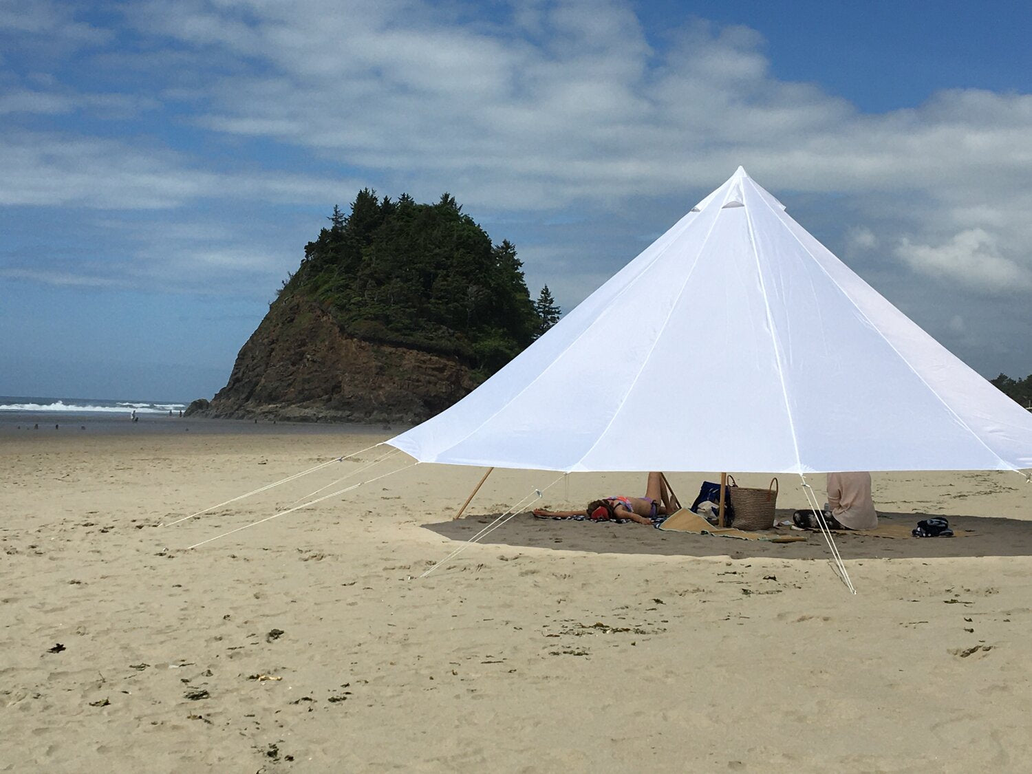A white shade canopy extends over two people on a beach to keep cool in the shade.