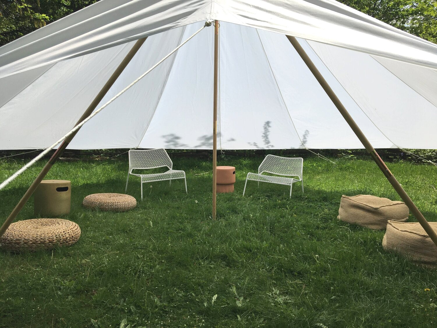 A canvas shade fly is set up over a green expanse of lawn with a variety of seating options around in order for people to keep cool in the shade.