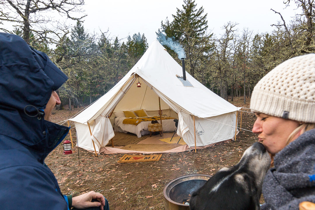two people and a dog sit outside a canvas tent that has a wood stove piping smoke out the top