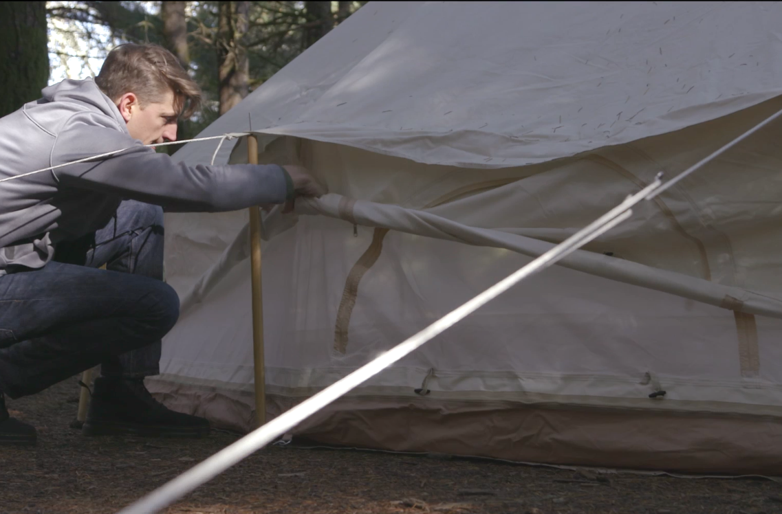 A person rolls up the walls of a canvas bell tent.