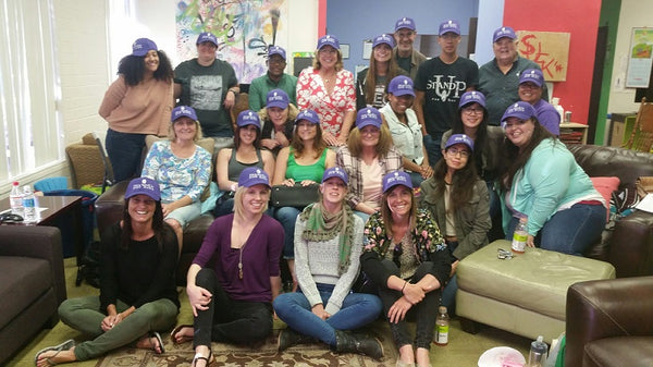 The Stand Up for Kids, San Diego team poses for a group photo, everyone is wearing a purple ball cap.