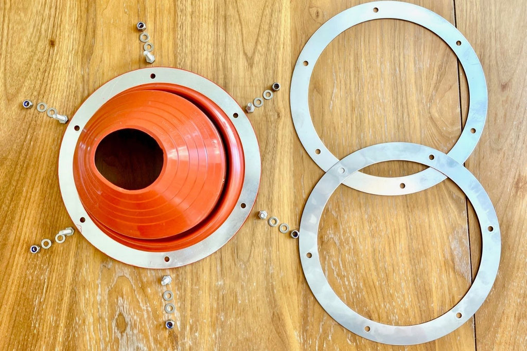 the contents of a stove jack flashing kit including an orange silicone flashing, stainless steel rings, and six sets of nuts, bolts, and washers
