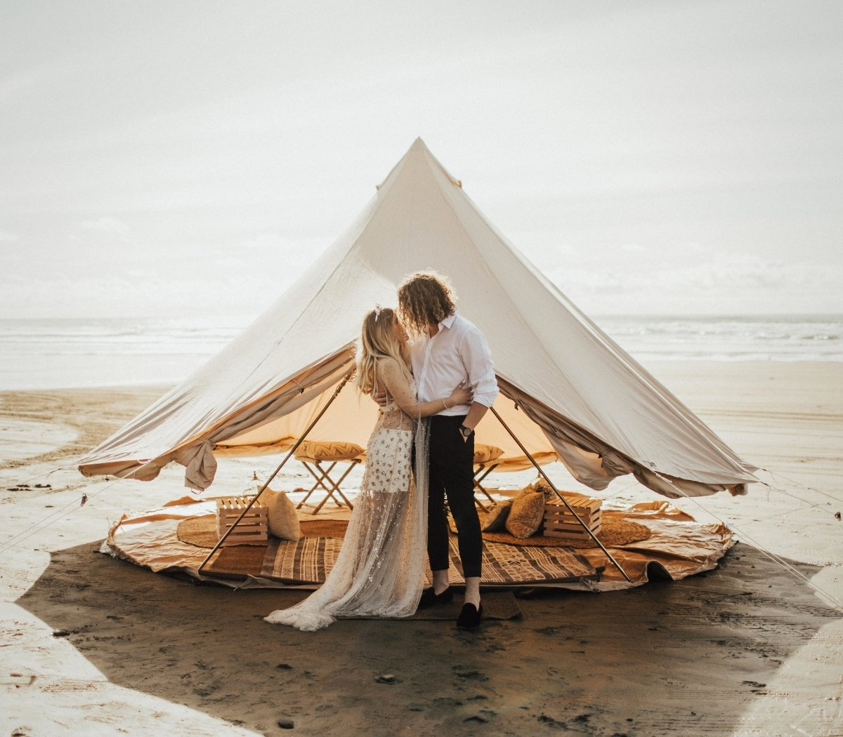 A fashionable couple stands on the beach in front of a canvas shade fly to keep cool in the shade.