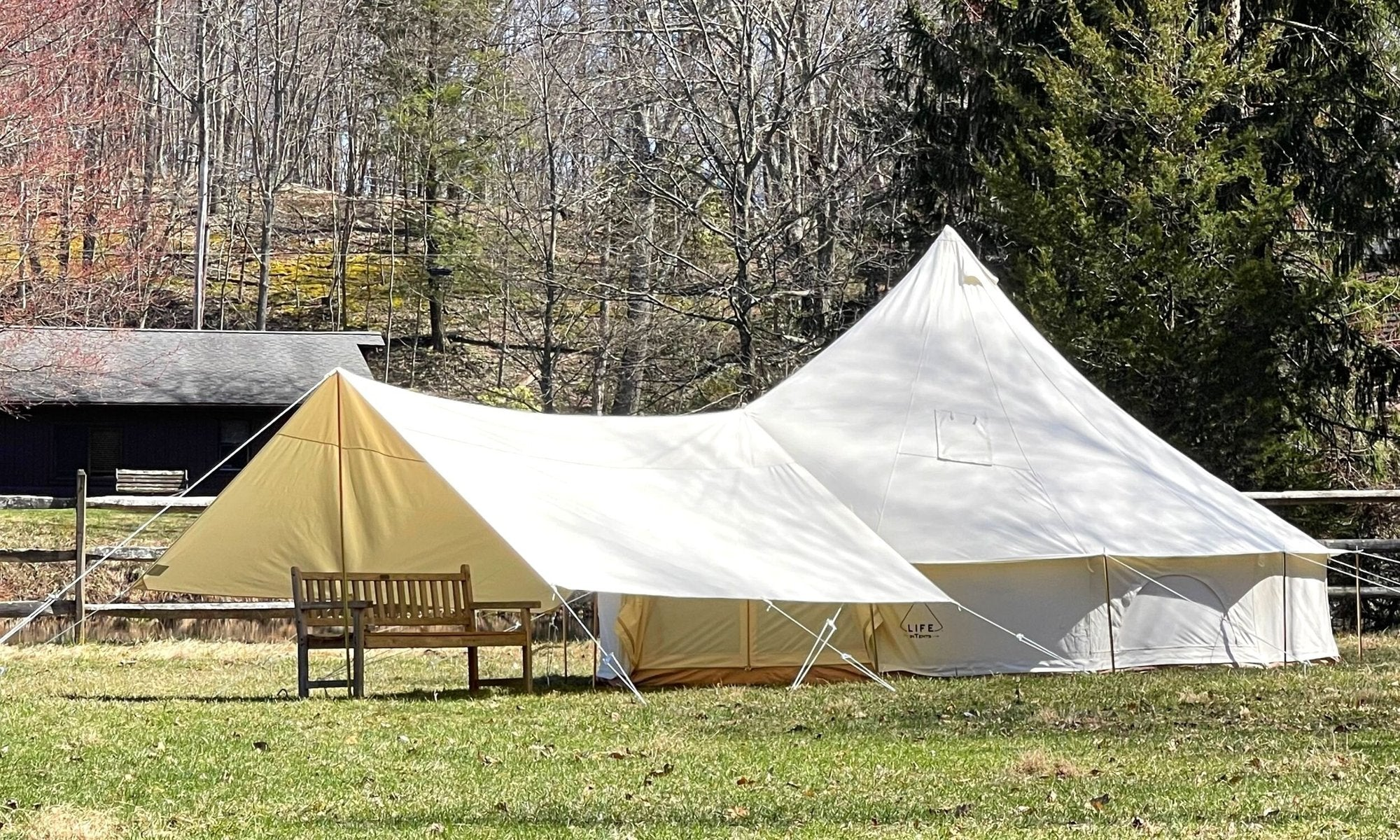 A white canvas bell tent that has an extended hallway connected to the front door, an awning for extra shade to keep cool.
